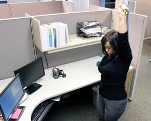 Yvette Medina stretches at her desk in Walnut Creek.