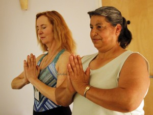 Manqueros and Lucila Valdes demonstrate a yoga posture.